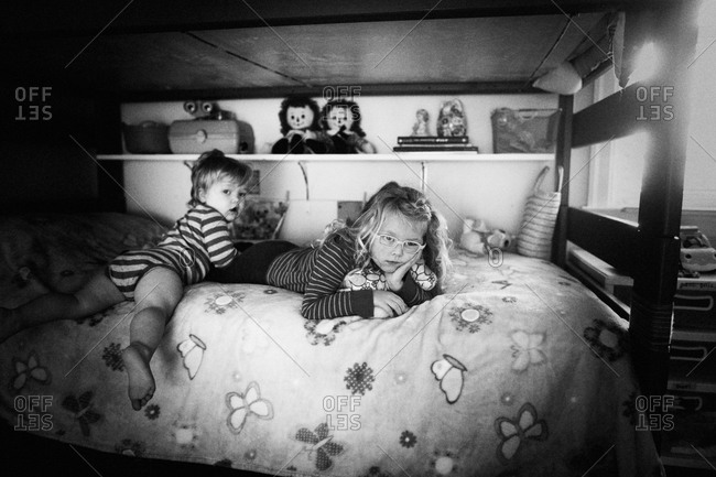 kids relaxing on the top bunk of a bunk bed