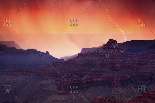 Lightning from a summer monsoon thunderstorm strikes a ridge in the Grand Canyon at sunset