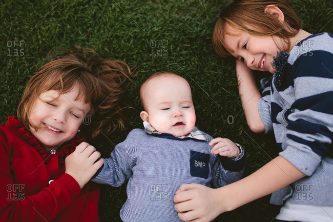 two kids and a baby lying in the grass together