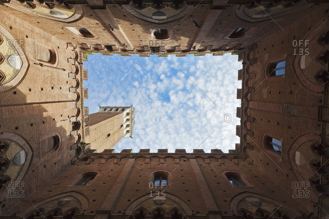 Italy, Tuscany, Siena, Torre del Mangia, Upward view of Palazzo Pubblico from courtyard