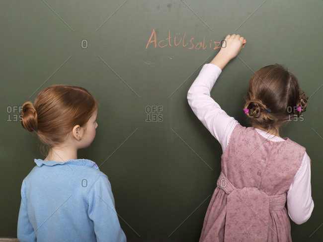 Girls standing in front of blackboard, writing, rear view