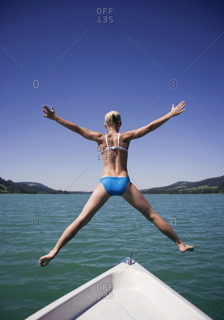 Teenage girl (13-15) jumping from boat into water, rear view
