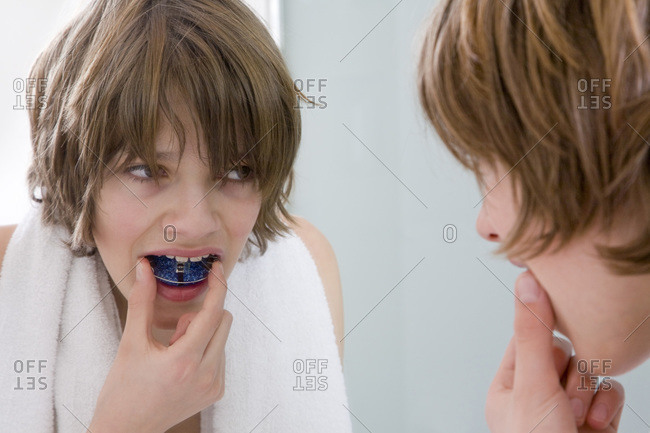 Germany, boy (12-13) putting in braces looking into mirror
