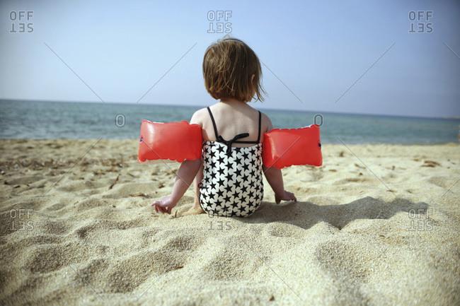 France, Corsica, Girl with armbands on beach
