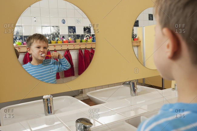 Germany, Boy (4-5) brushing his teeth in front of mirror, portrait