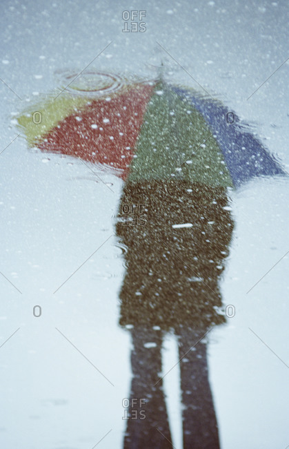 Germany, Bavaria, Huglfing, Young woman with umbrella reflecting in water puddle