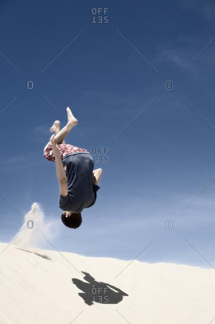 France, Teenage boy jumping on sand dune
