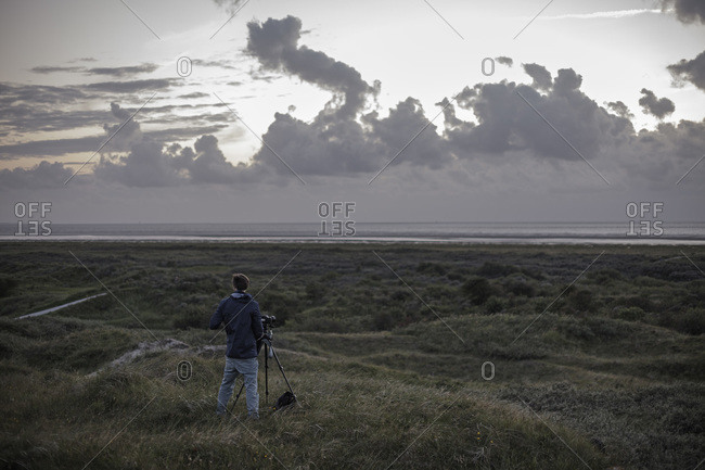 Netherlands, Man standing with camera at North sea