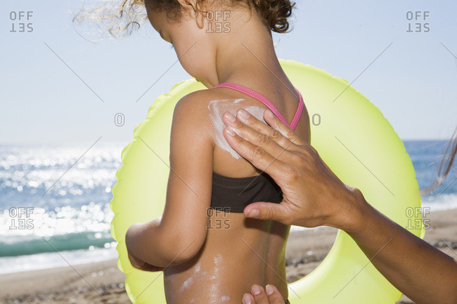 France, Corsica, Mother applying sun cream on daughter's (2-3) back