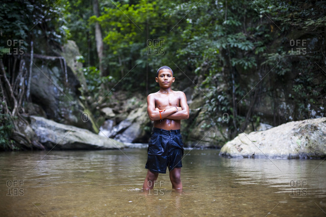 A portrait of a young boy standing with folded arms in shallow water near the remote village of chuao, venezuela