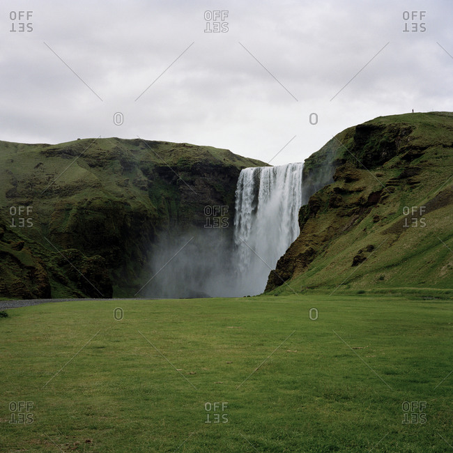 A waterfall cascading over lush green grass in Iceland