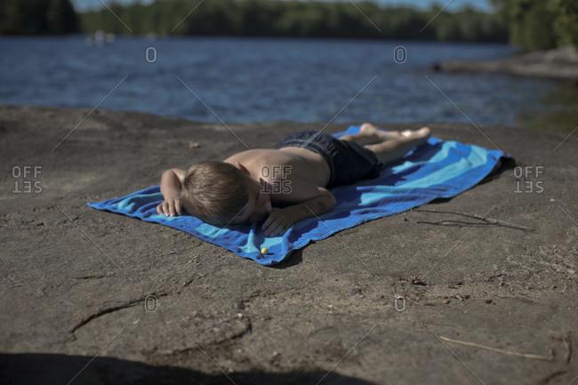 Boy Lying on Beach Towel on Rocks by Lake, Muskoka, Ontario, Canada