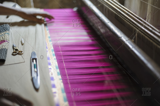 Hand feeling threads in loom