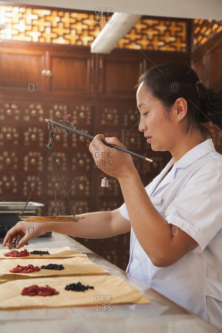 Chinese woman weighing herbs in traditional pharmacy
