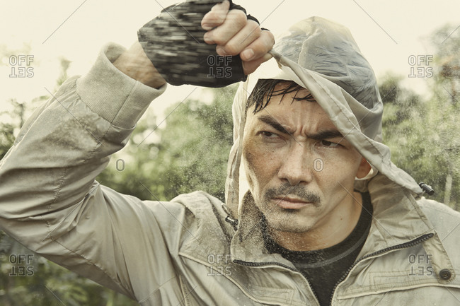 Asian man wearing hood in rain