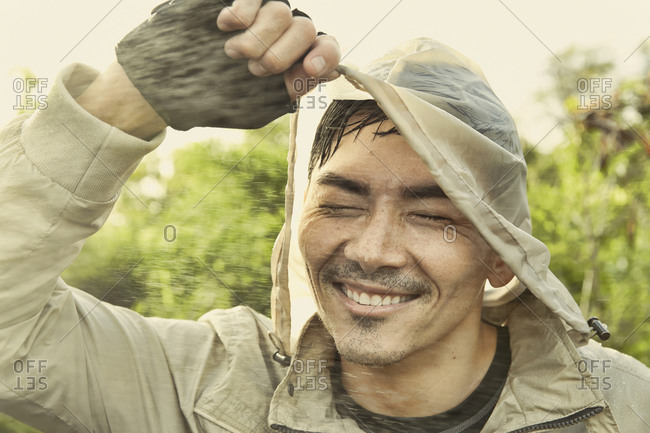 Asian man wearing hood in rain