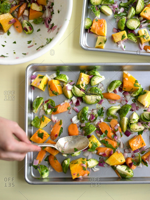 Close up of hand spreading vegetables on baking sheet