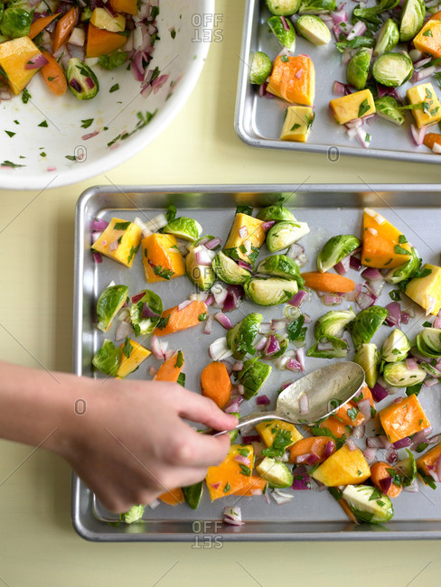 Overhead view of hand spreading vegetables on baking sheet