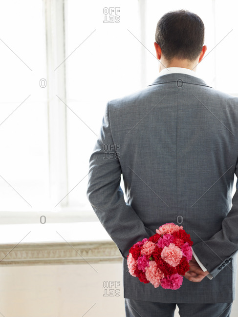 Rear view of man standing with bunch of flowers in hand
