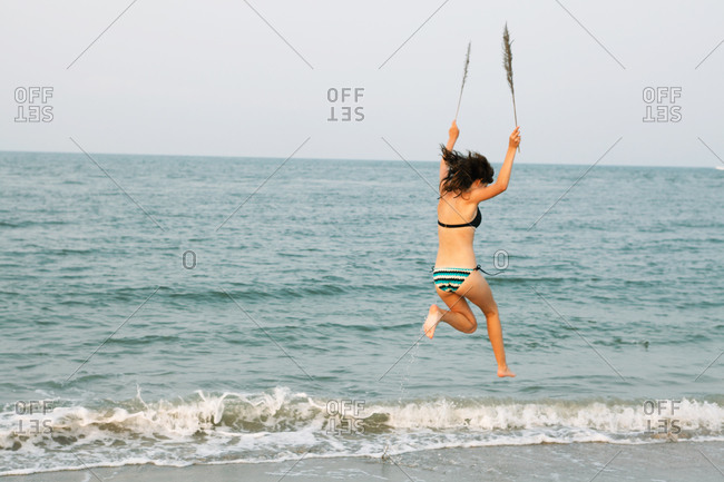 A woman jumps on the shore while holding branches