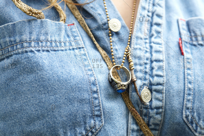 A girl wears a class ring on a chain