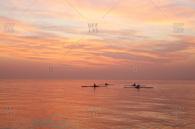 Rowers on a lake during sunset