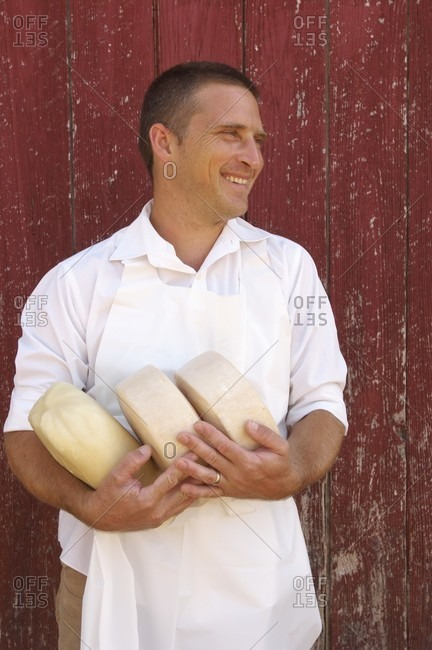 Cheese Maker in Apron Holding Goat Cheese Rounds