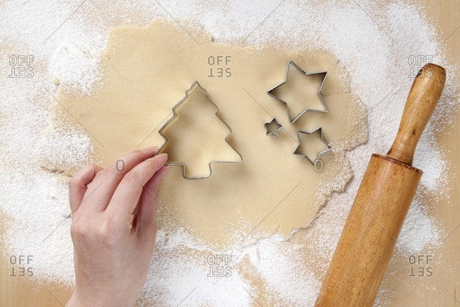 Hand Placing Christmas Tree Cookie Cutter on Rolled Out Cookie Dough; Star Cookie Cutters