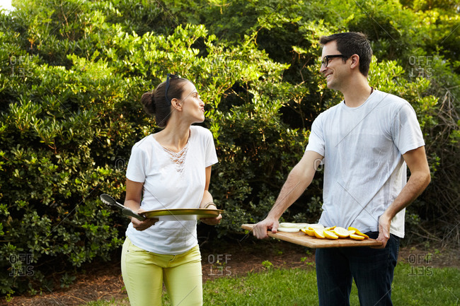 Couple standing in garden and holding trays