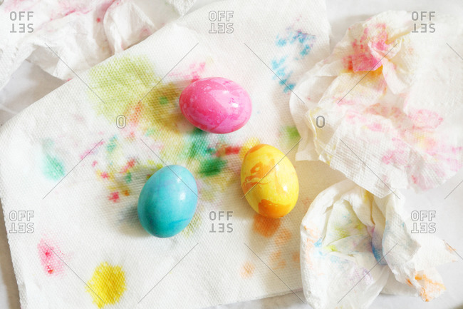 Freshly painted eggs drying on paper towels