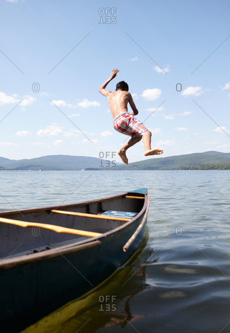 young boy jumps off canoe