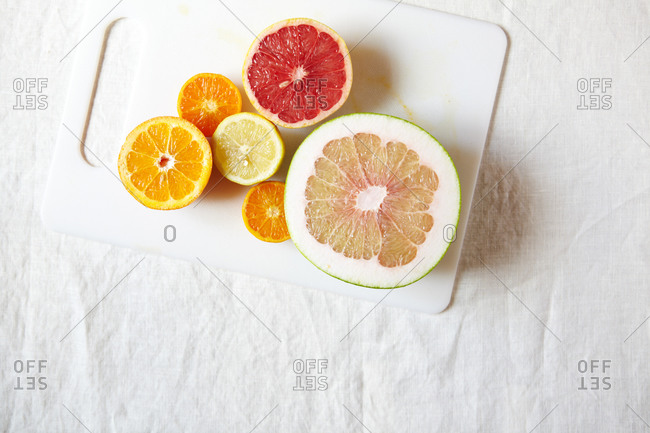 citrus fruits sliced in half on a cutting board