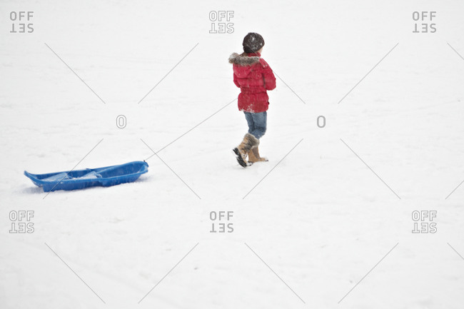 kid pulling sled through the snow