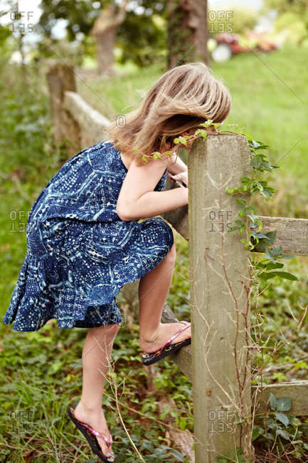 side view of a little girl climbing on a fence