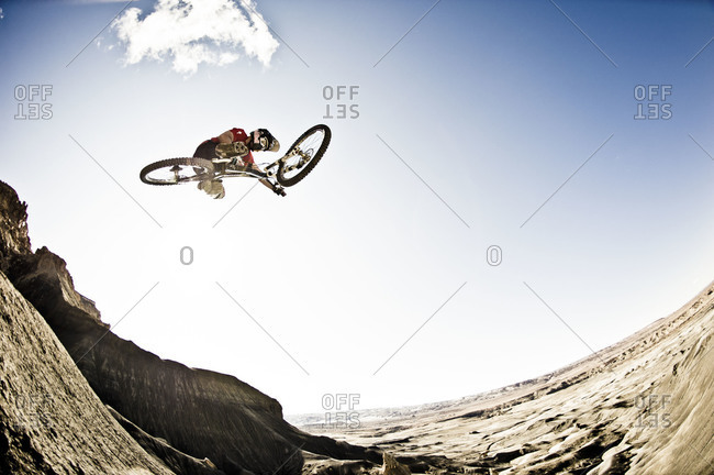 view from below of a man freestyle mountain bike jumping