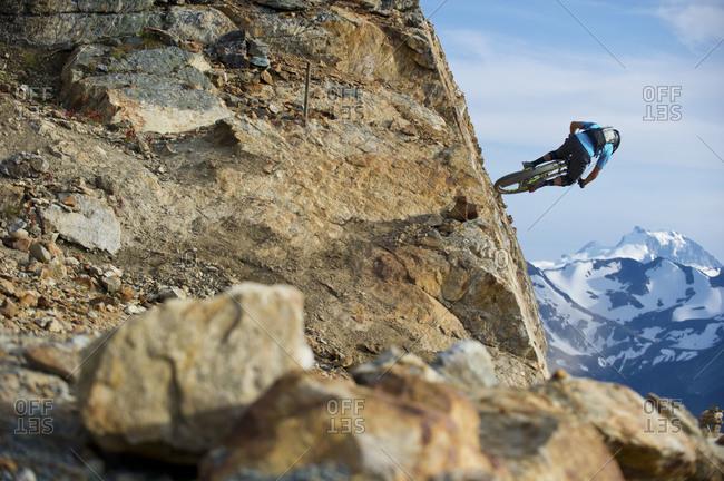 a man rides his mountain bike through the hills of Whistler, BC, Canada