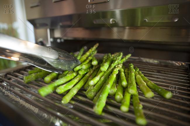 Tongs reaching for asparagus