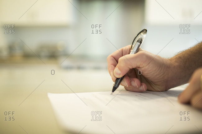 Close up of a man signing a document