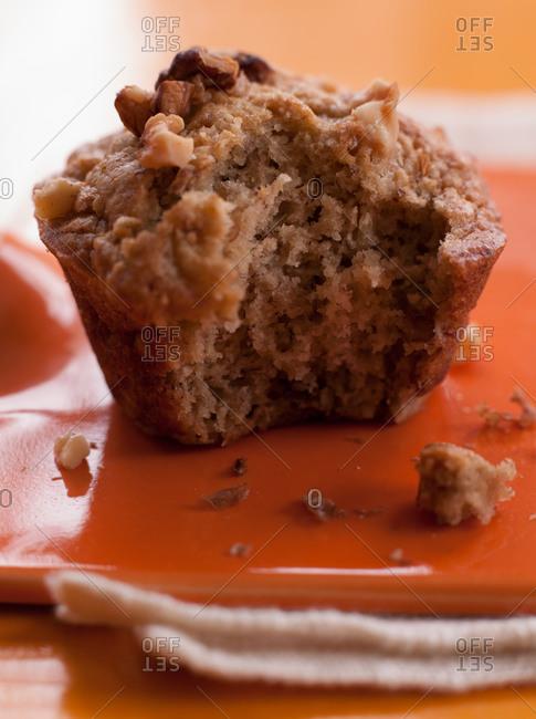 Close-up of walnut muffin on orange plate