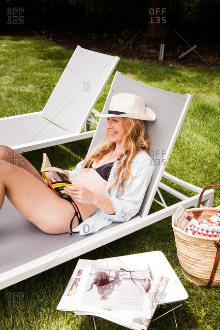 Happy Caucasian woman relaxing in deck chair with book outdoors