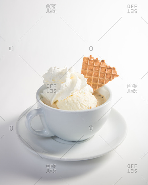 Cappuccino served with whipped cream, ice cream and waffle
