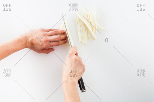 Woman's hands chopping celery root on white background