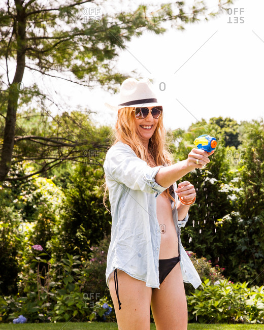 Happy Caucasian woman playing with water pistol outdoors