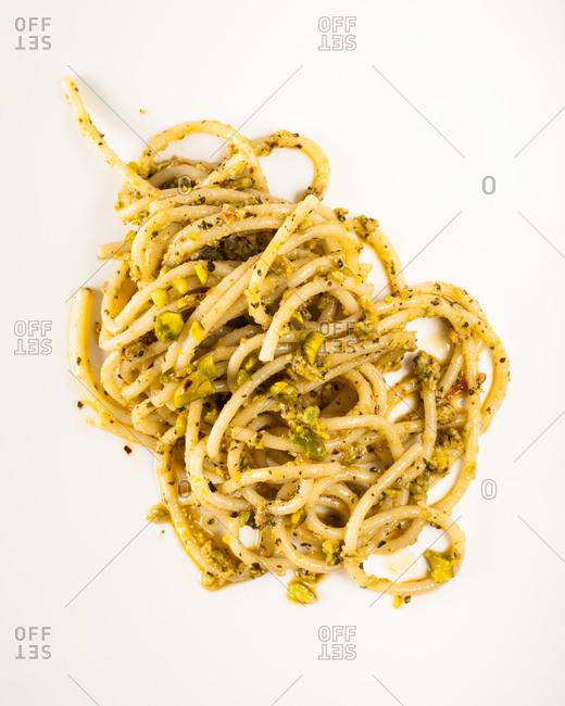 Tasteful spaghetti with pesto sauce displayed on white background