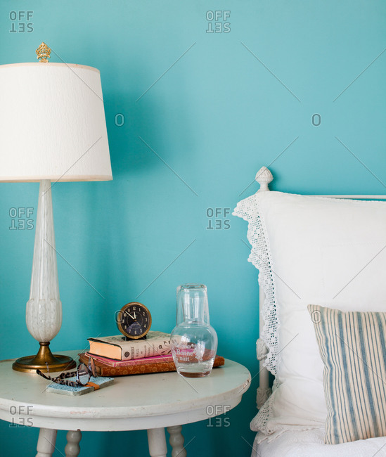 Shabby chic bedroom interior with items on nightstand