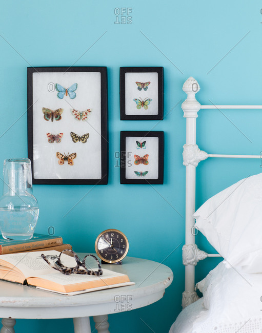 Modern bedroom interior with butterfly pictures, books and clock
