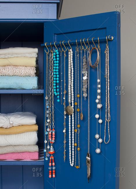 Necklaces hanging on opened closet door