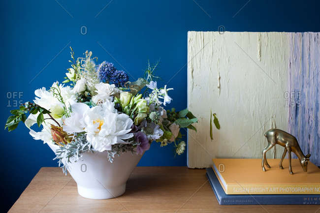 Wildflowers in vase in front of blue wall