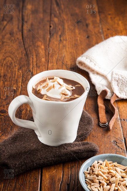 Cup of hot chocolate with whipped cream and almond shavings