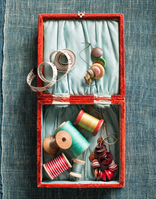 Opened sewing kit on textile background